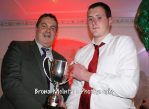 Ronan Gillan, the captain of the Reserve team receiving the Reserve Championship from Jim Murray