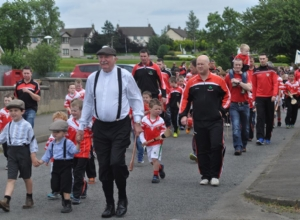 BRENDAN MCGARRY PAST HURLER LEADING THE PAGEANT IN PERIOD COSTUME WITH HIS GRANDSONS