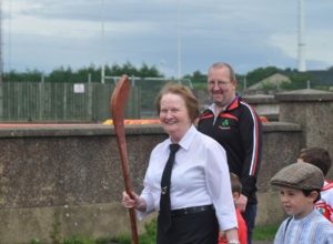 LOU MCKINLEY PAST CAMOGIE PLAYER LEADING THE PAGEANT IN OLD TIME CAMOGIE GEAR INCLUDING OLD HURL