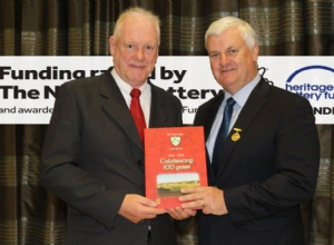 CHAIRMAN JOHN CAMPBELL PRESENTING THE GAA PRESIDENT WITH THE LOUGHGIEL CENTENARY BOOK funded by the Hertiage Lottery Fund